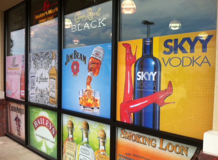 Auslagefenster mit Werbeplakaten für alkoholische Getränke