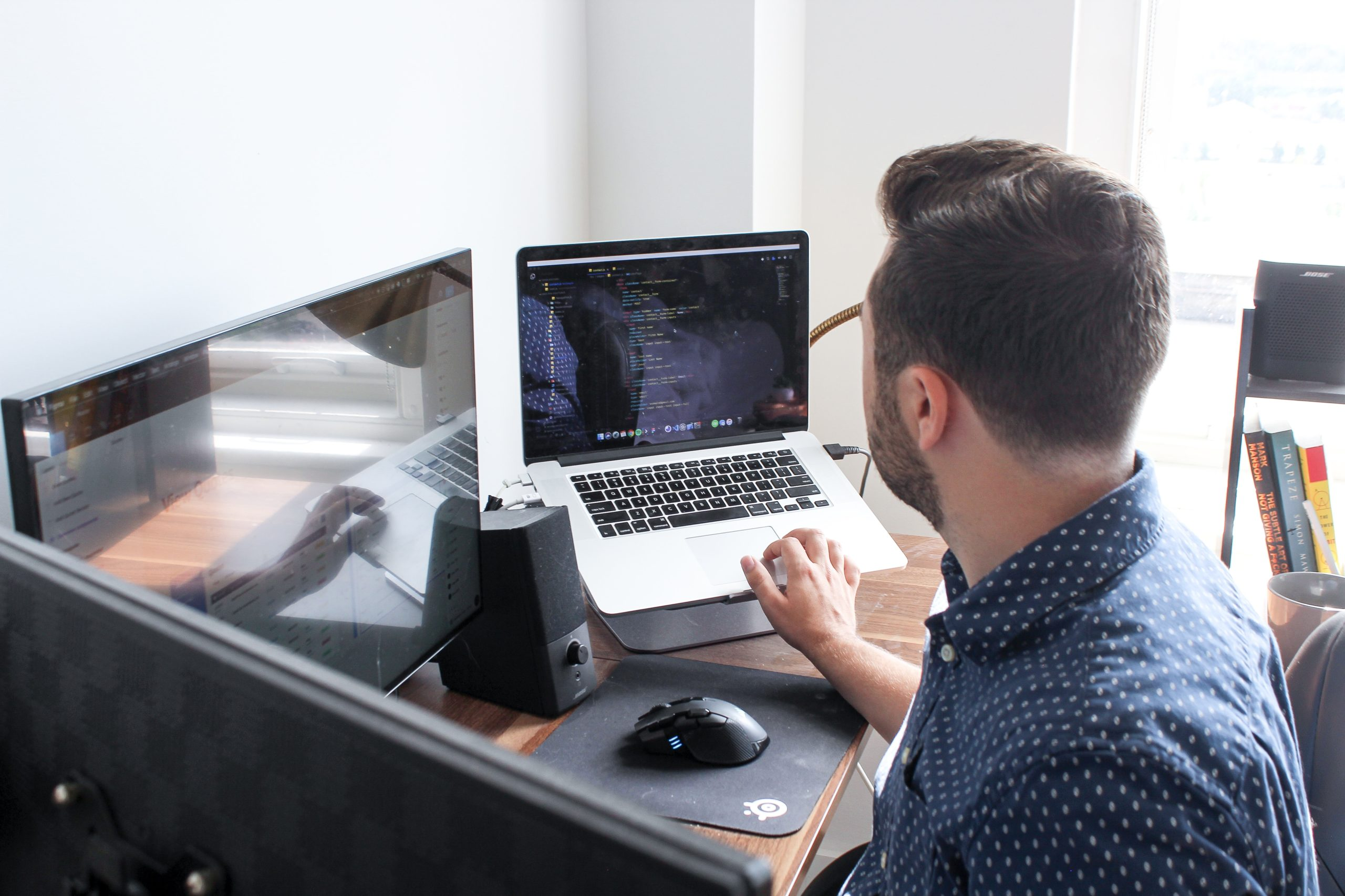 Man sitting in front of a laptop and desktop