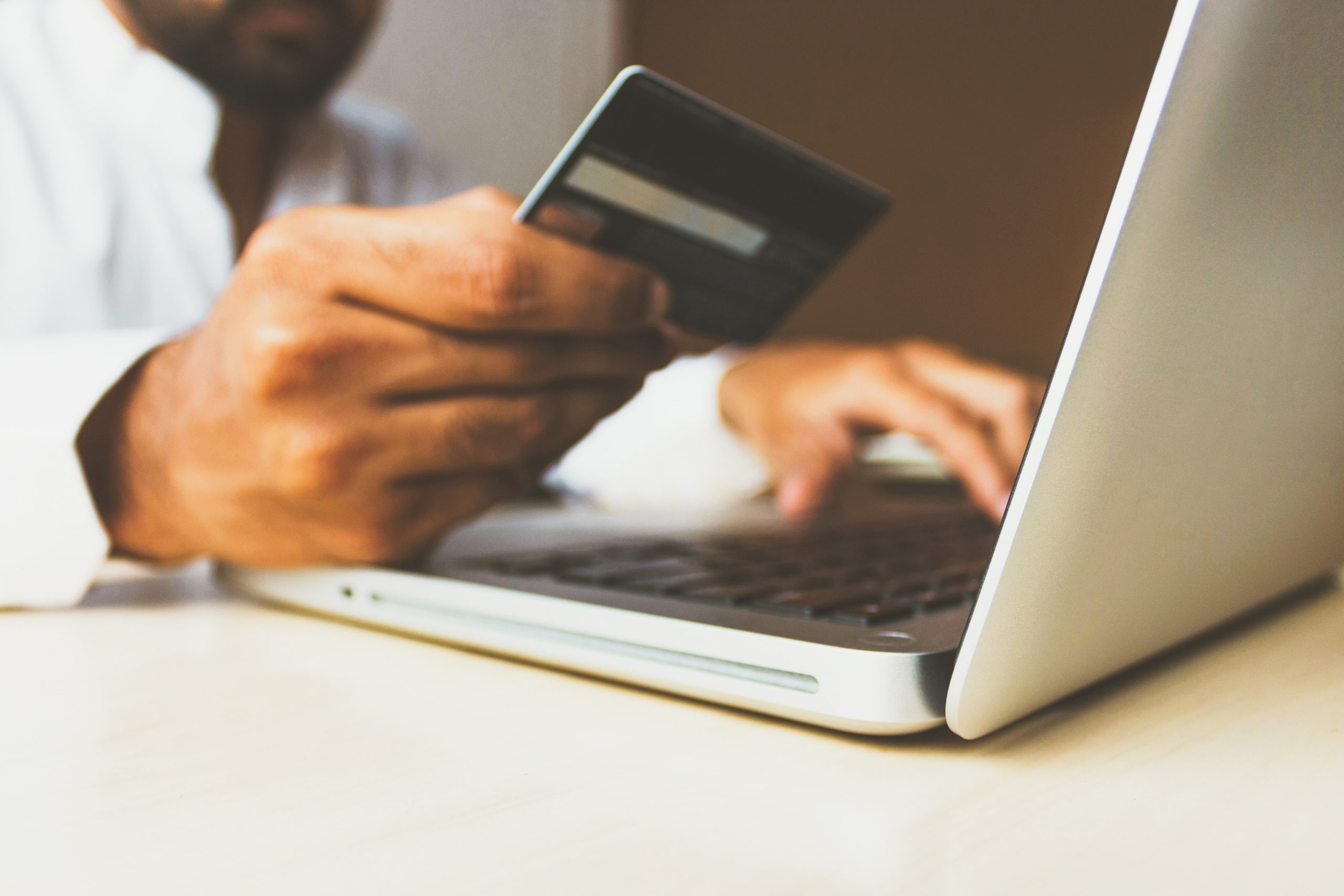 Man in front of a laptop holding up a credit card