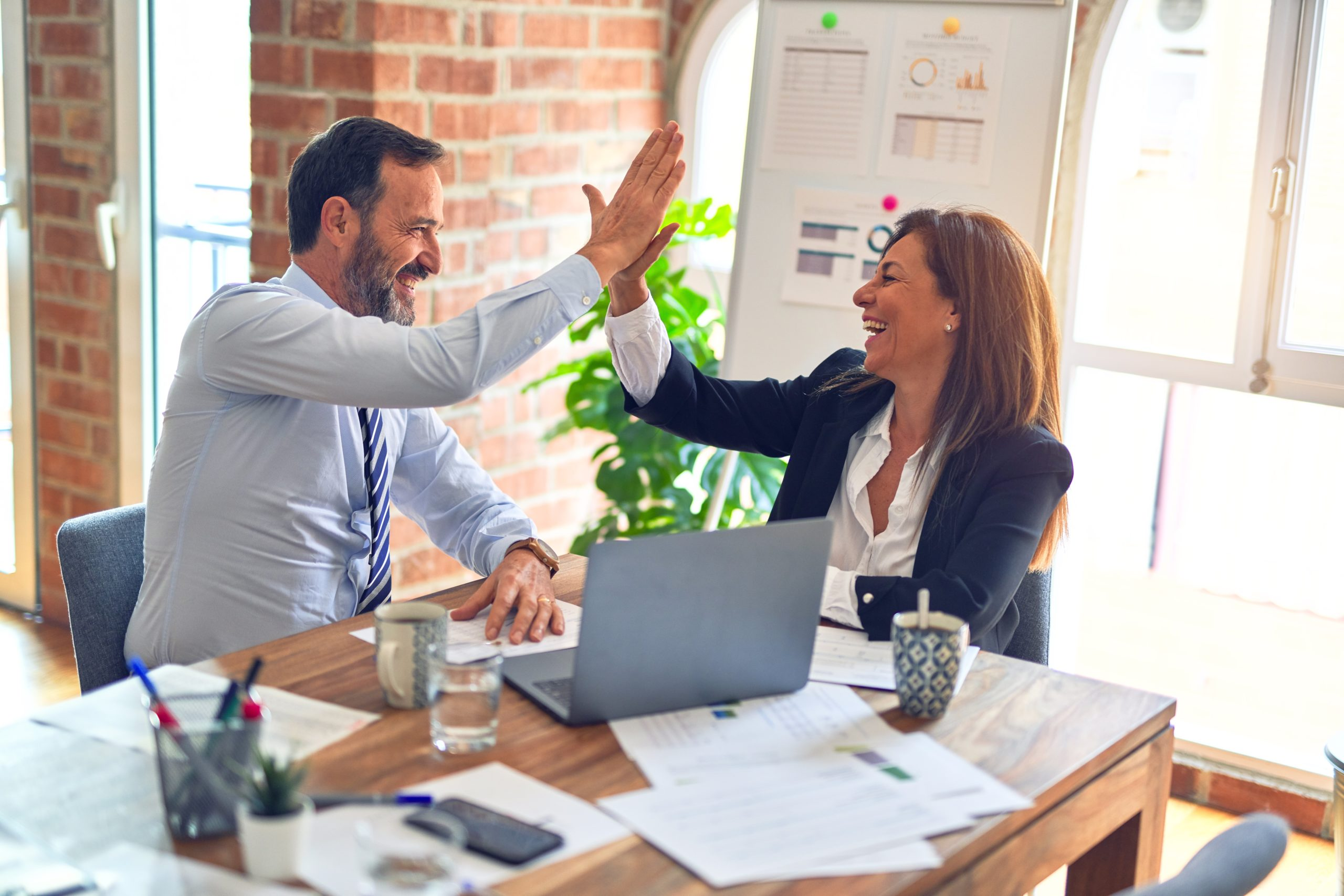 Two colleagues sharing a high-five after a personal meeting